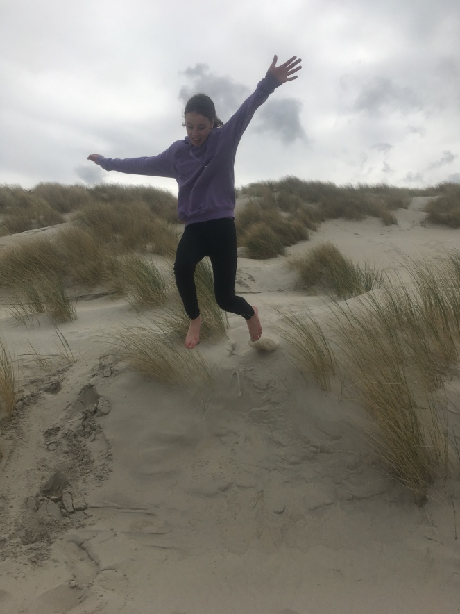 Girl jumping off a sand dune in Terschelling