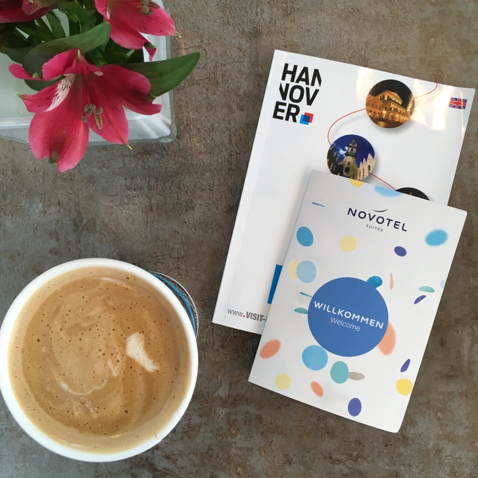 Hannover guide book, Novotel key card and cup of coffee on a table
