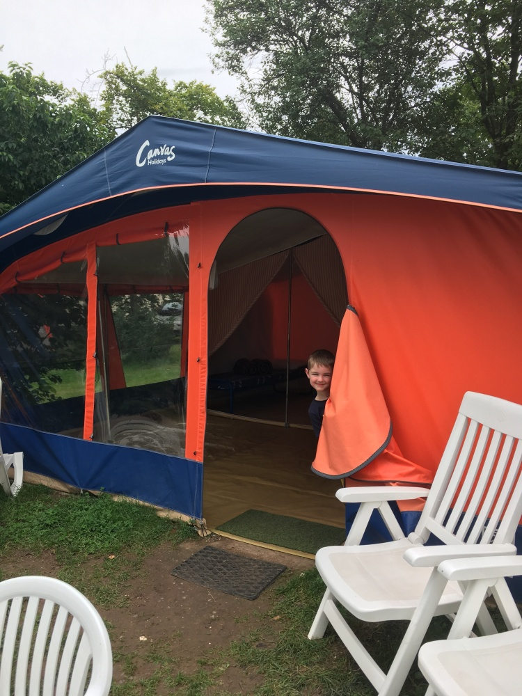Orange Canvas Holidays tent with little boy peeking out.