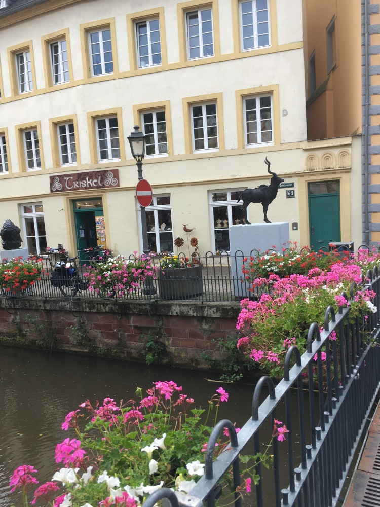 Things Helen Loves, view across a bridge adorned with flowers to a statue of an elk in Saarburg