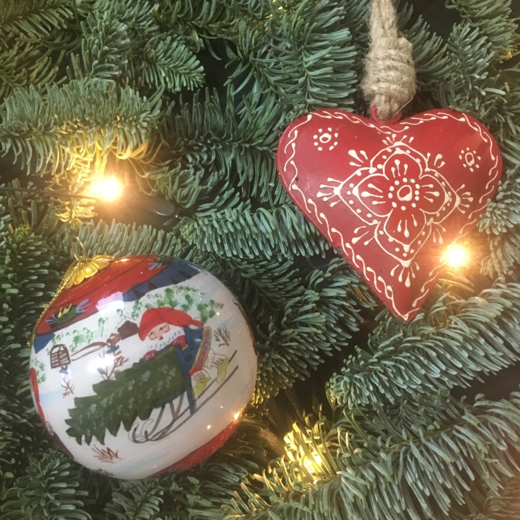 Things Helen Loves, Bauble painted with elves in Norwegian style and red hanging heart on evergreen branches.