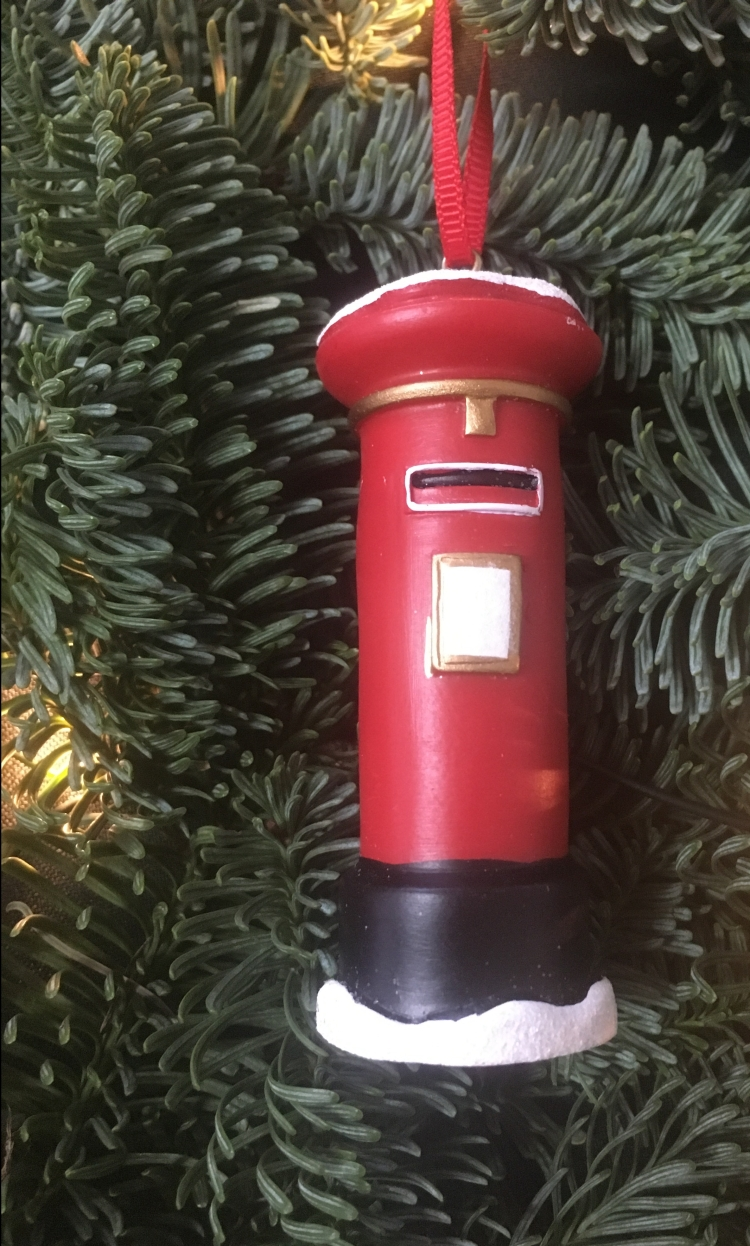 Things Helen Loves, Red Post box tree ornament on evergreen branch background.