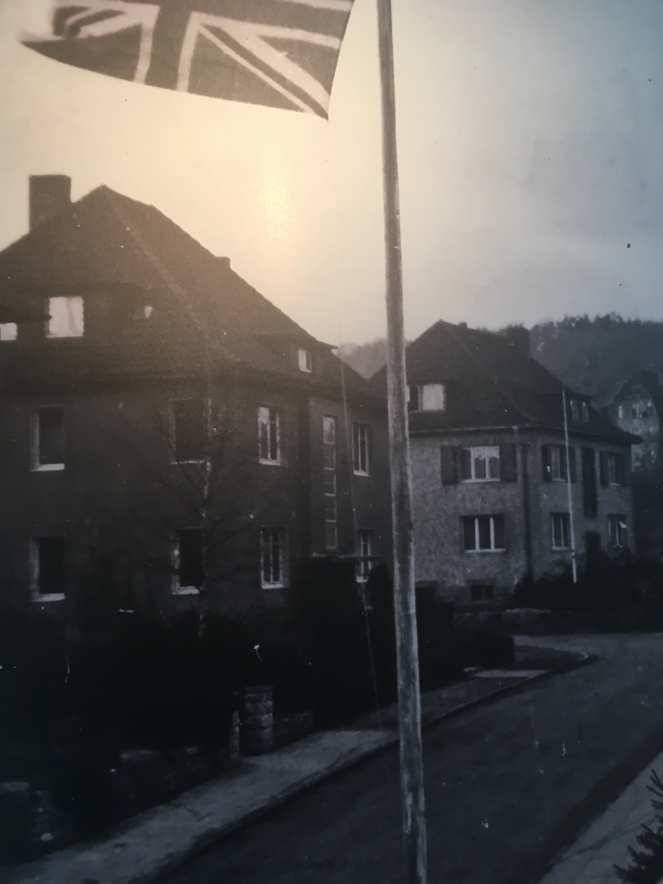 Things Helen Loves, black and white image of a flag flying over a street of German housing.