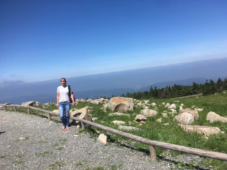 Things Helen Loves, author standing on mountain top with forest and hill views