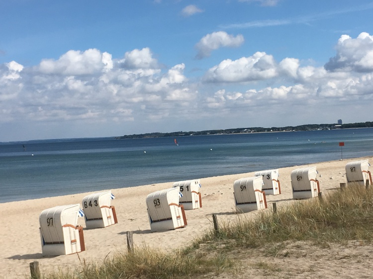 Things Helen Loves, image of beach chairs on sand with blue skies and blue sea.