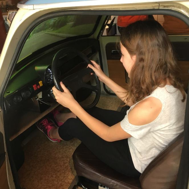 Things Helen Loves, image of girl driving Trabi simulator in Berlin