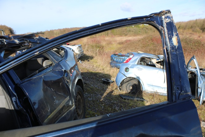 Things Helen Loves, Image of blue and silver scrap cars on salisbury plain, viewed through the window of another car