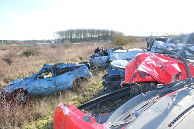 Things Helen Loves, image of wrecked cars piled up on Salisbury Plain Training Area. Scrub land and trees to background