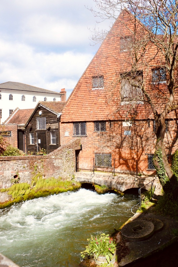 Things Helen Loves, image of Winchester Mill against a cloudy sky. Rushing stream and flowers to the foreground.