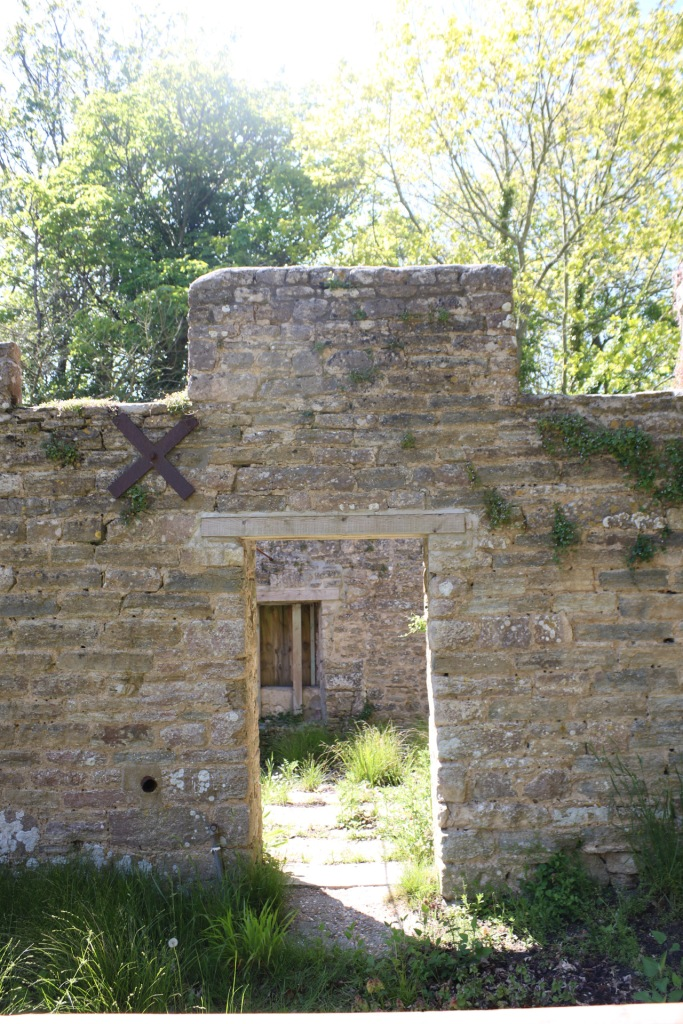 Things Helen Loves Image of ruined cottage , stone doorway and remains of walls with green trees in the sunlight to the background