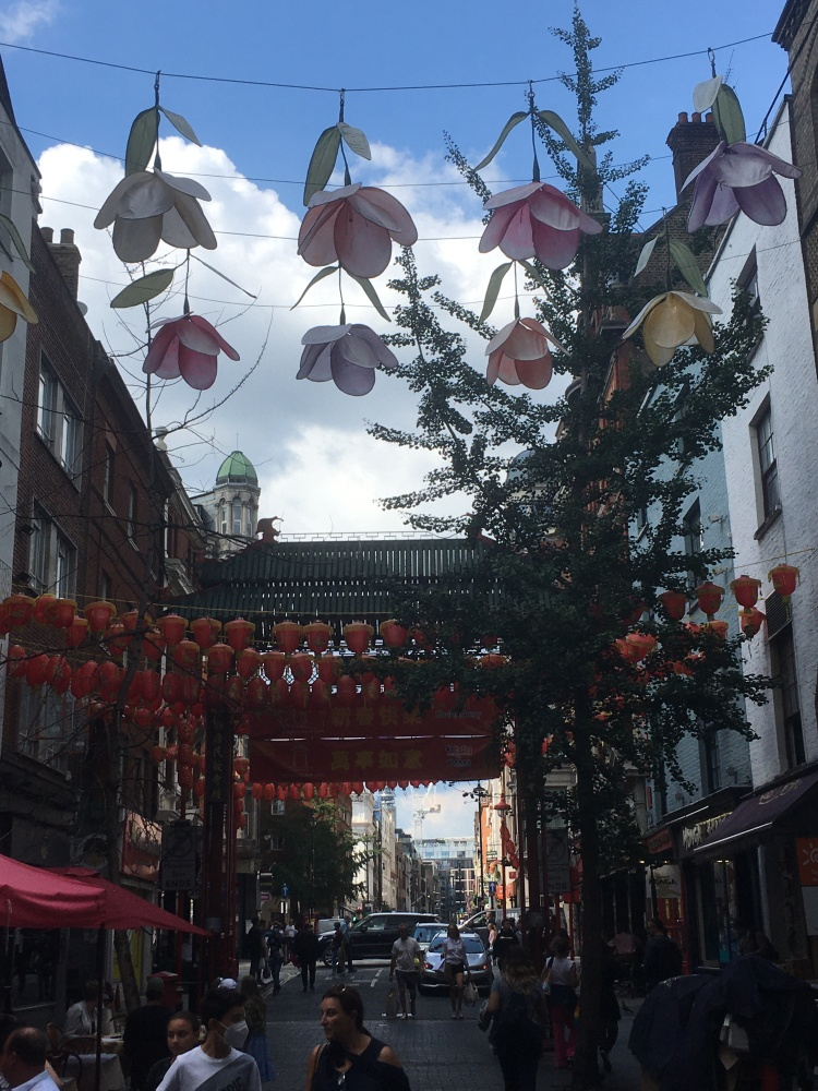 Things Helen Loves image of street in Chinatown London with traditional lanterns and flowers hung overhead between buildings