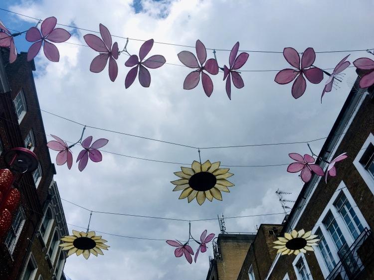 Things Helen Loves, Sunflowers and pink flowers displayed between buildings in Wardour St London